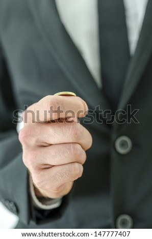 Closeup  of businessman hand tossing a coin. - stock photo
