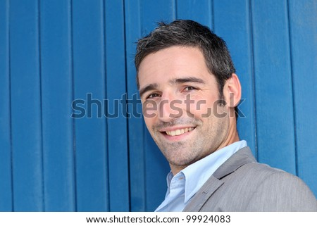 Closeup of businessman leaning on blue background - stock photo