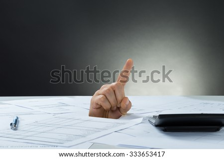 Closeup of businessman's hand emerging from documents - stock photo