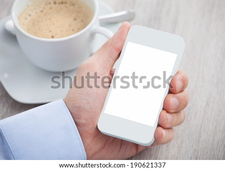 Closeup of businessman's hand holding cellphone with blank screen on desk - stock photo