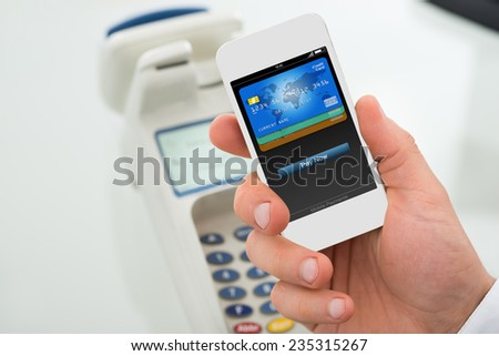 Closeup of businessman's hand paying through mobilephone in office - stock photo