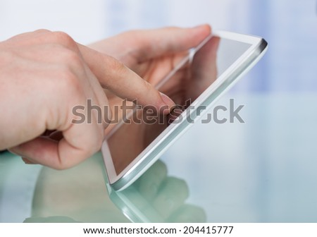 Closeup of businessman's hands using digital tablet in office - stock photo