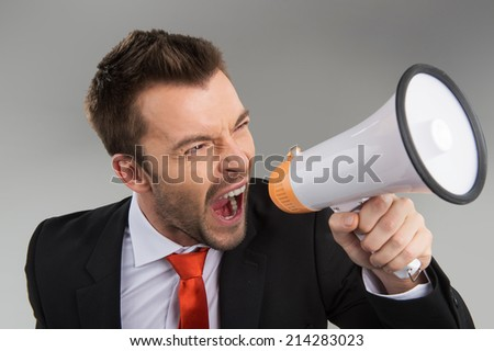 Closeup of businessman screaming in megaphone isolated on grey background. Businessman speaking loud through megaphone - stock photo