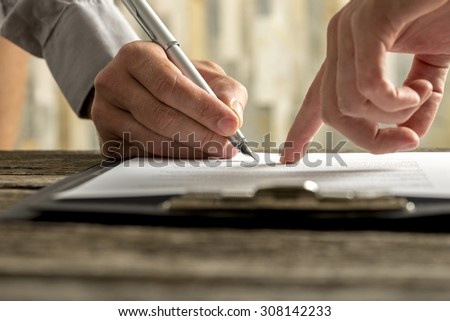 Closeup of businessman showing his new business partner where to sign an agreement or contract with fountain pen  on rustic wooden desk.  - stock photo