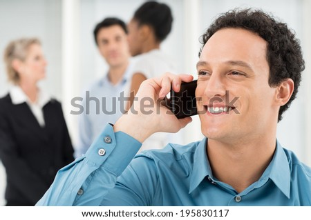 Closeup Of Businessman Talking On Cell Phone In Front Of Colleague - stock photo