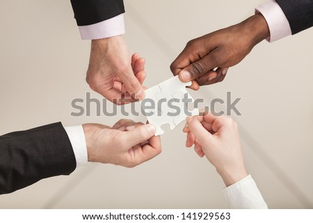Closeup of businesspeople about to put four puzzle pieces together. Top View. Close up - stock photo