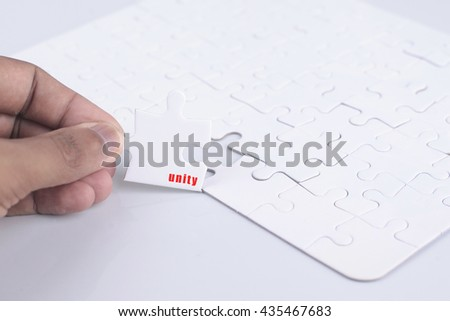 Closeup of businesspeople about to put four puzzle pieces with unity word together.  - stock photo
