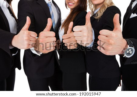 Closeup of businesspeople gesturing thumbs up against white background - stock photo