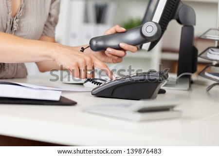 Closeup of businesswoman pressing number button at office desk - stock photo