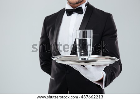 Closeup of butler in tuxedo and gloves holding silver tray with glass of water - stock photo