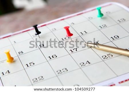Closeup of calendar page with marked important days and pen - stock photo
