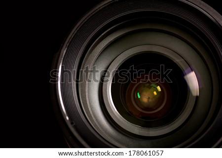 Closeup of camera lens over black background - stock photo