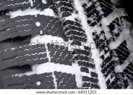 closeup of car tire with winter tread in snow - stock photo