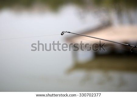 Closeup of carbon fishing tackle with lure on natural blur background outdoor male hobby angling vacations relax, horizontal picture  - stock photo