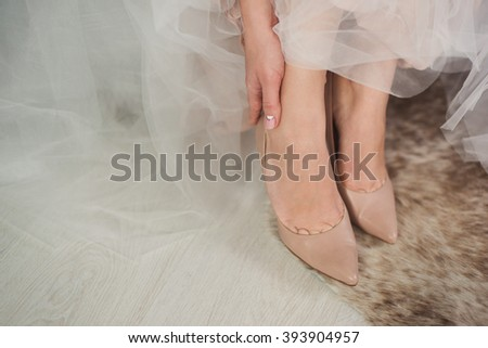 closeup of caucasian bride put on her beige leather shoes - stock photo