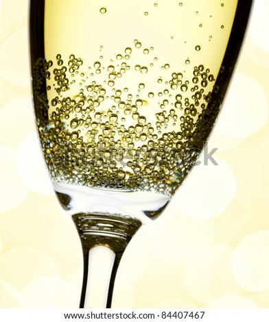 closeup of champagne flute, abstract lights background, focus on bubbles - stock photo