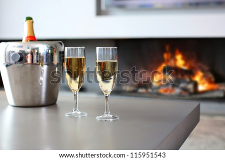 Closeup of champaign glasses set by fireplace - stock photo