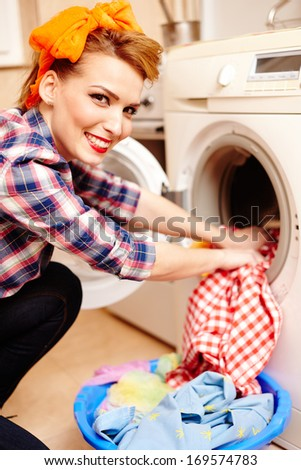 Closeup of cheerful housewife putting the laundry into the washing machine - stock photo