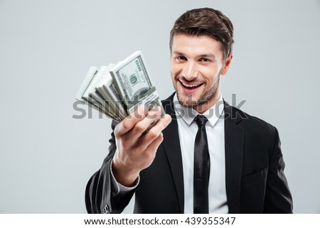 Closeup of cheerful young businessman holding money over white background - stock photo