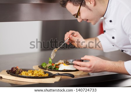 Closeup of chef garnishing egg dish with sauce in commercial kitchen - stock photo