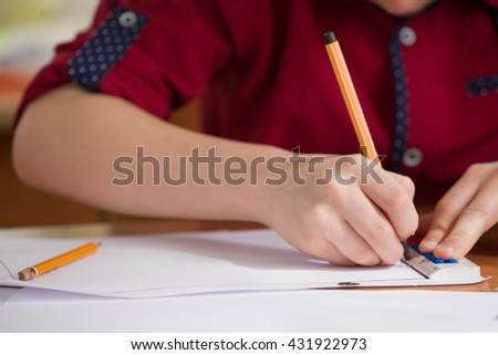 Closeup of child's hands drawing a ruler. Boy's doing his homework at the desk. Child at the desk in school  - back to school, learning and studying concept - stock photo