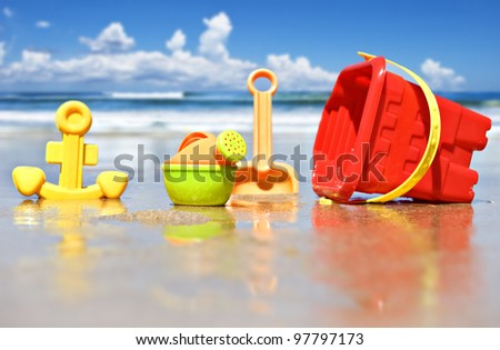 Closeup of children's beach toys at the beach - focus on the watering can - stock photo