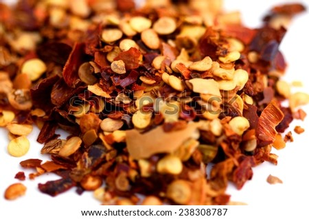 Closeup of chili pepper flakes on white background. - stock photo