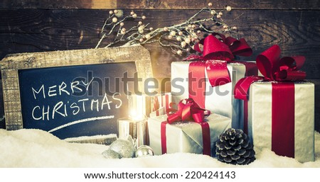 Closeup of Christmas gifts with candles and slate. - stock photo