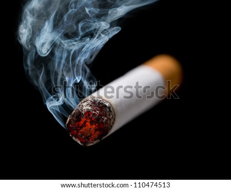 Closeup of cigarette with wisp of smoke - stock photo