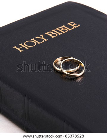 Closeup of closed bible and wedding bands - stock photo