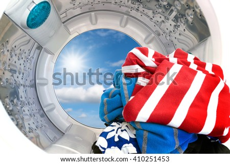 Closeup of cloths Inside the washing machine with the sun and sky background. - stock photo