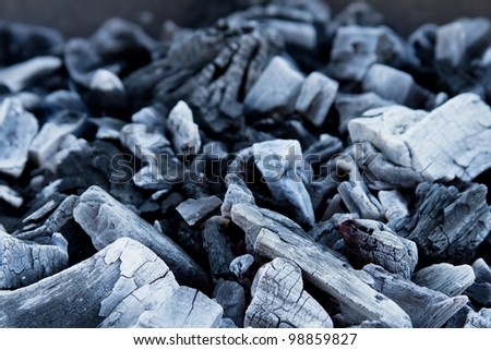 Closeup of coal in a grill with shallow depth of field - stock photo