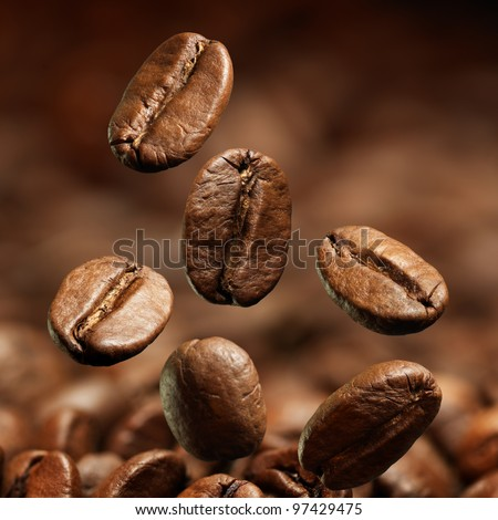 Closeup of coffee beans with focus on one - stock photo