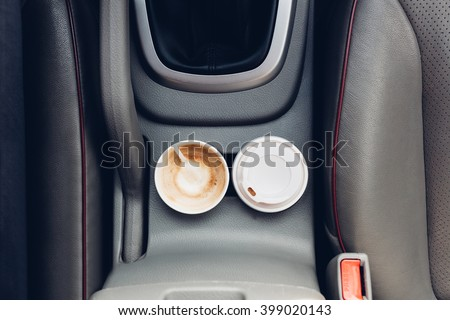 Closeup of coffee cups inside car holder between seats - stock photo