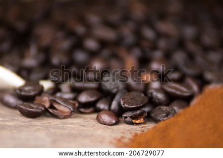 closeup of cofffe beans with coffee powder on wooden table selective focus - stock photo