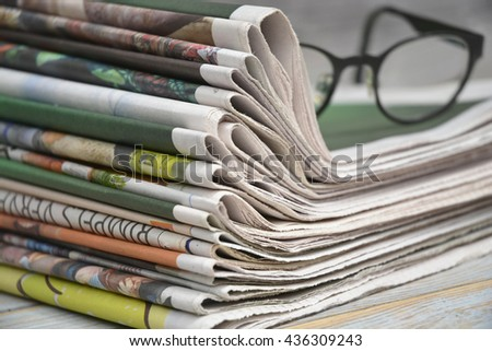 Closeup of color stacked newspapers on a wooden table background - stock photo