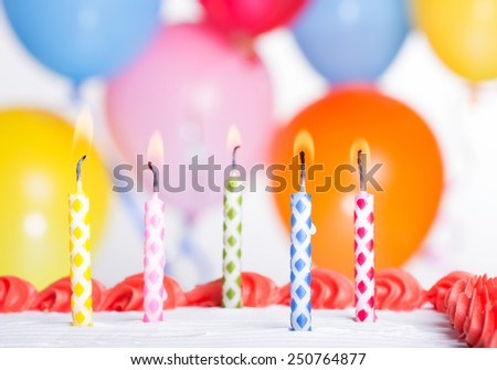 Closeup of colorful birthday candles on a cake with balloons in background - stock photo