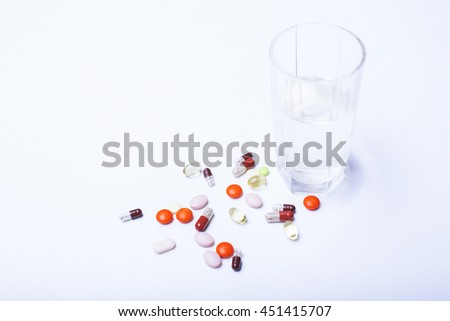 Closeup of colorful pills and glass of water on bright white surface - stock photo