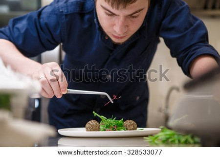 Closeup of concentrated male chef garnishing food in kitchen - stock photo