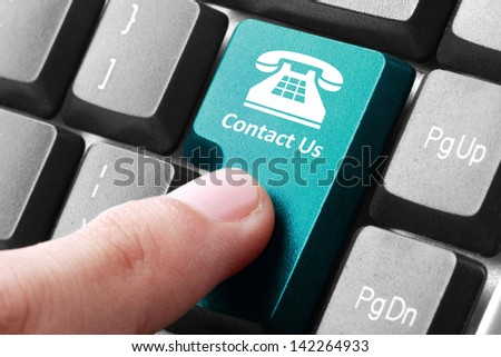 Closeup of contact us button on the keyboard - stock photo