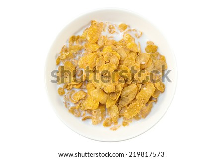 Closeup of corn flakes and milk in a bowl viewed from above, isolated on white background - stock photo