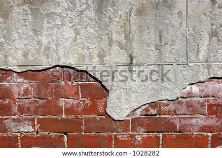 Closeup of cracked stucco on brick wall. - stock photo