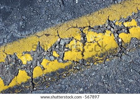 Closeup of cracked yellow line on asphalt road. - stock photo