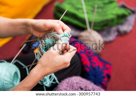 closeup of crafting hands with wool and needles - stock photo