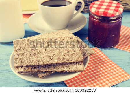 closeup of crispbread in a plate, a cup of coffee, a bottle with milk and a jar of jam on a rustic blue wooden table, with a cross-process effect - stock photo