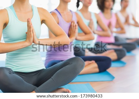 Closeup of cropped sporty women with joined hands at a bright fitness studio - stock photo