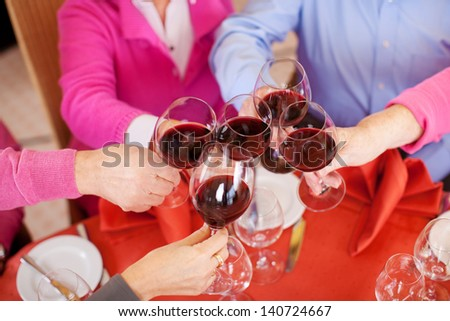 Closeup of customers toasting wine glasses at restaurant table - stock photo