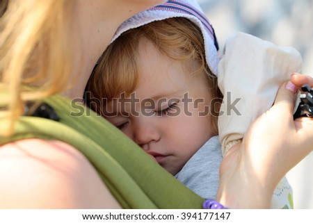 Closeup of cute beautiful carefree innocent baby boy deep sleeping on hands of mother sunny day outdoor, horizontal picture - stock photo