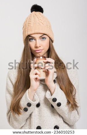 Closeup of cute Caucasian brunette teenage girl with beige knitted beanie hat and coat holding takeaway coffee cup. No retouch. - stock photo