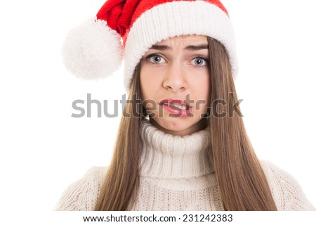 Closeup of cute confused teenage girl with Santa Claus hat. Pretty young woman worried and scared making facial expression isolated on white background.  - stock photo